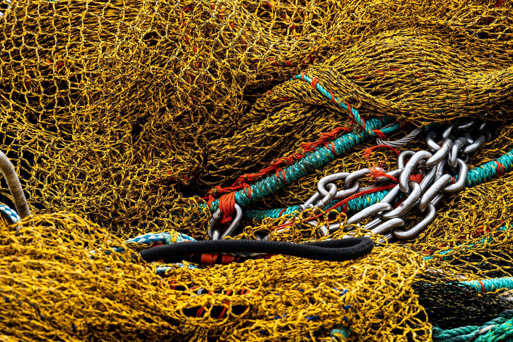 Grundschleppnetzfischerei: Nahaufnahme eines gelben Fischernetzes. Stahlketten und Seile liegen darüber