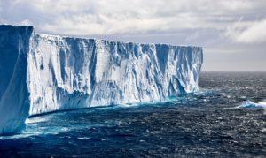 Weddell-Meer, ein gewaltiger Eisberg ragt aus dem Meer. Am Himmel bilden sich dicke Wolken