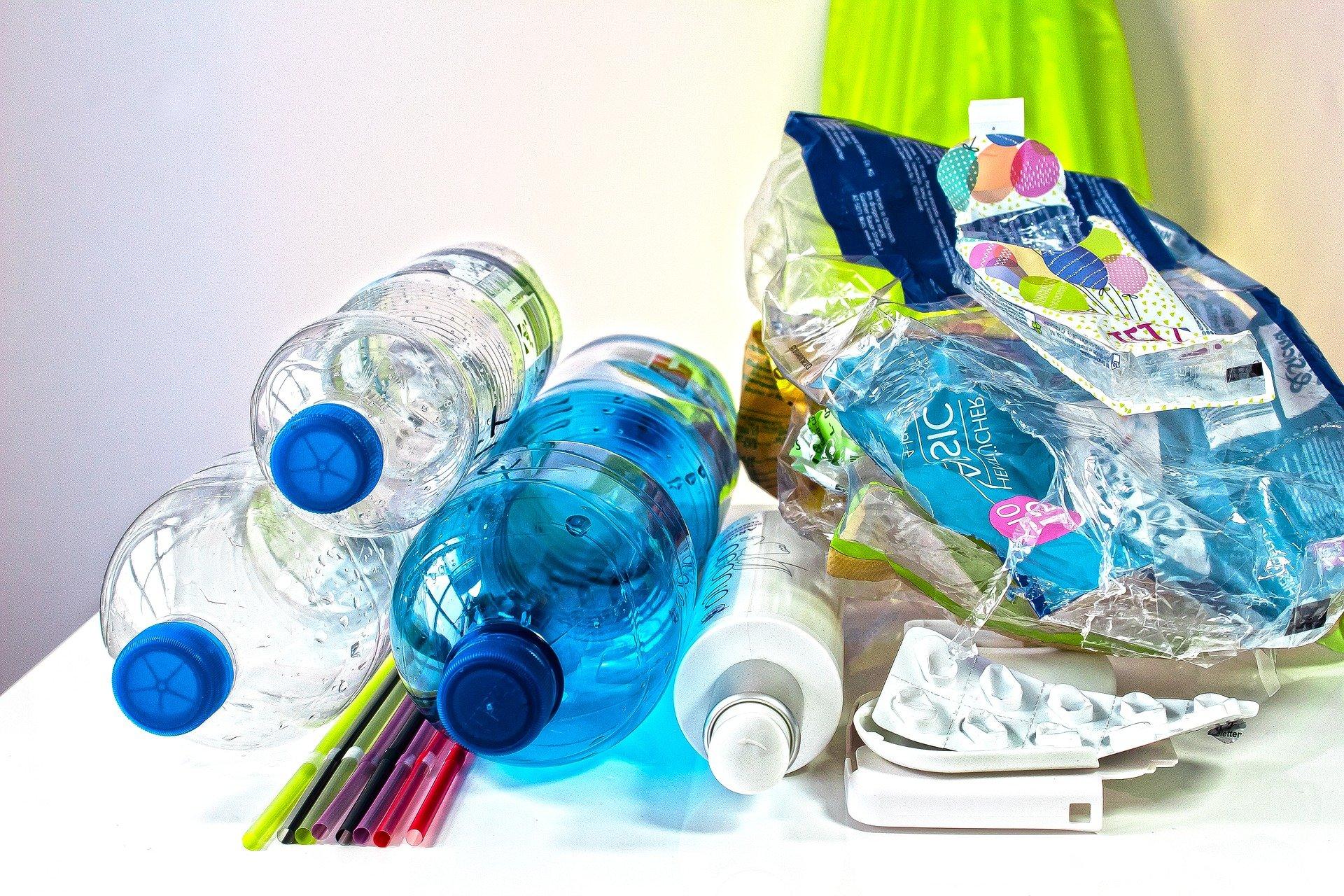 Alltagsgegenstände aus Plastik, wie Wasserflaschen und Plastikstrohhalme sind übereinander gestapelt