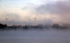 Ein Windkraftwerk im Morgennebel. Es ist nur schwach im Hintergrund zu erkennen