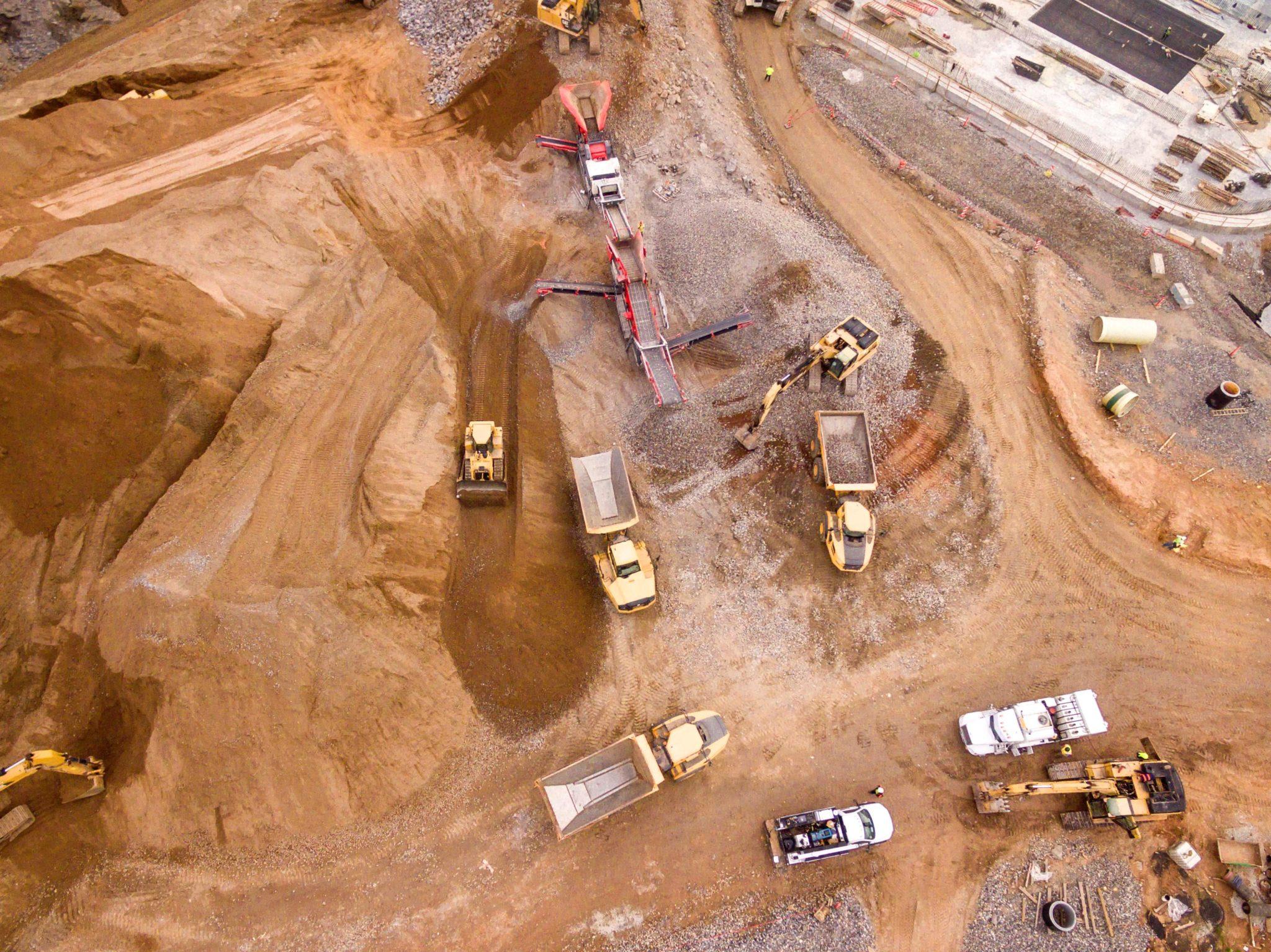 Eine Luftaufnahme von vielen Baggern und Lastwägen beim Rohstoff-Abbau.