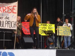 Luisa Neubauer steht auf einer Bühne mit einem Mikrofon, hinter ihr stehen andere Jugendliche mit Plakaten