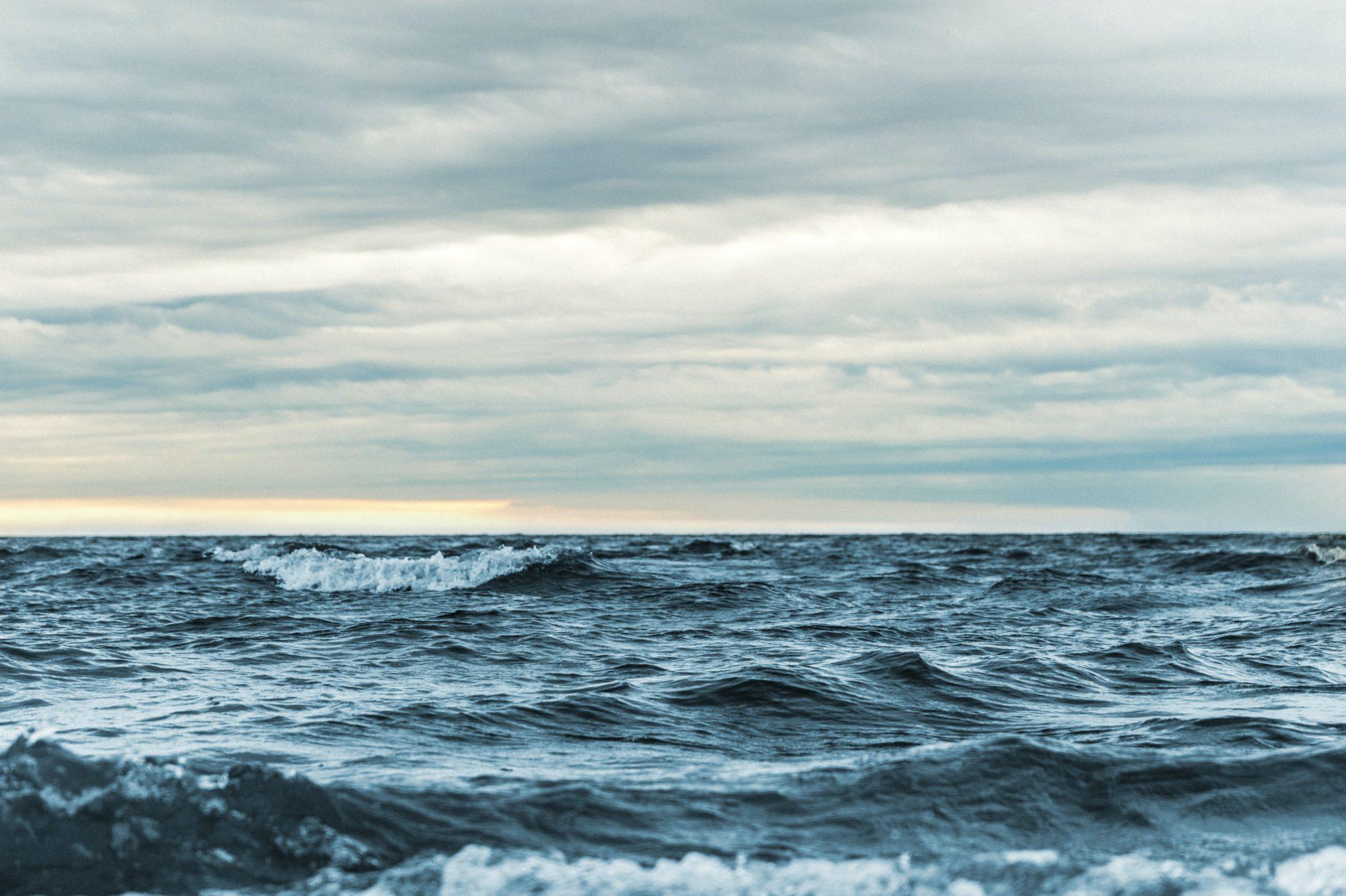 Ein dunkles Meer mit vielen kleinen Wellen, der Horizont ist bewölkt