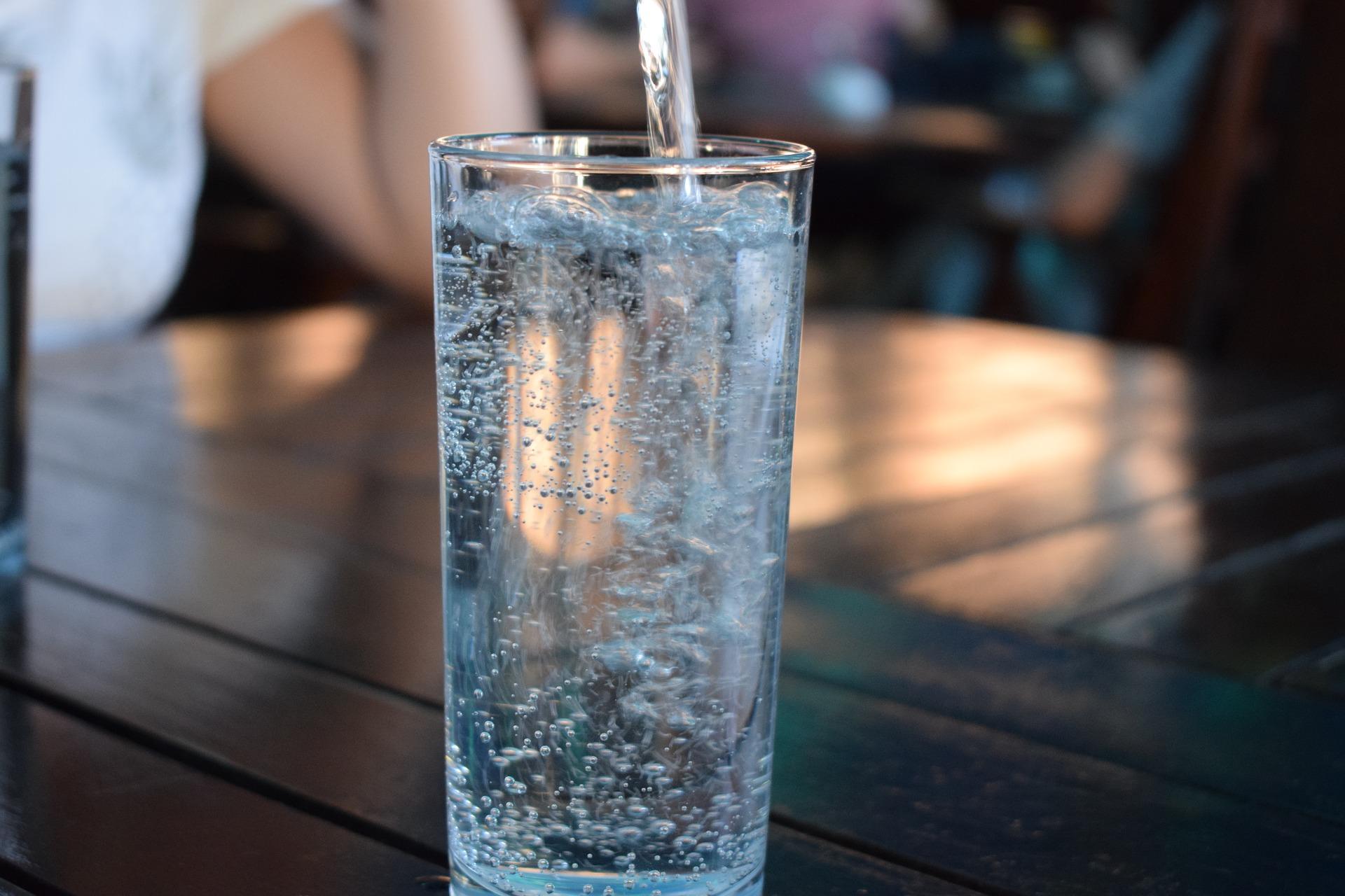 Ein Glas steht auf einem Holztisch. Es wird sprudeliges Mineralwasser eingeschenkt