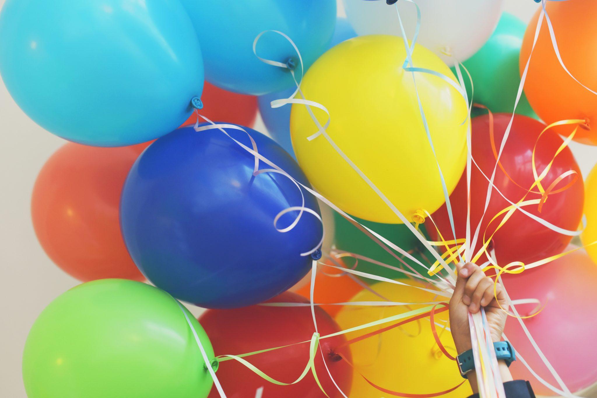 Eine Hand hält viele bunte Luftballons