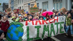 Viele Kinder demonstrieren mit einem großen Plakat für Fridays for Future
