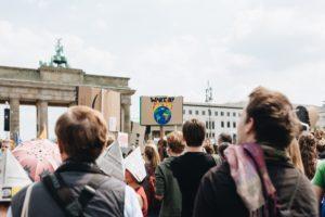 Eine Fridays for Future-Demonstration. Viele Menschen stehen vor dem Brandenburger Tor. Ein Demoschild mit einer brennenden Erde ragt aus der Menge heraus