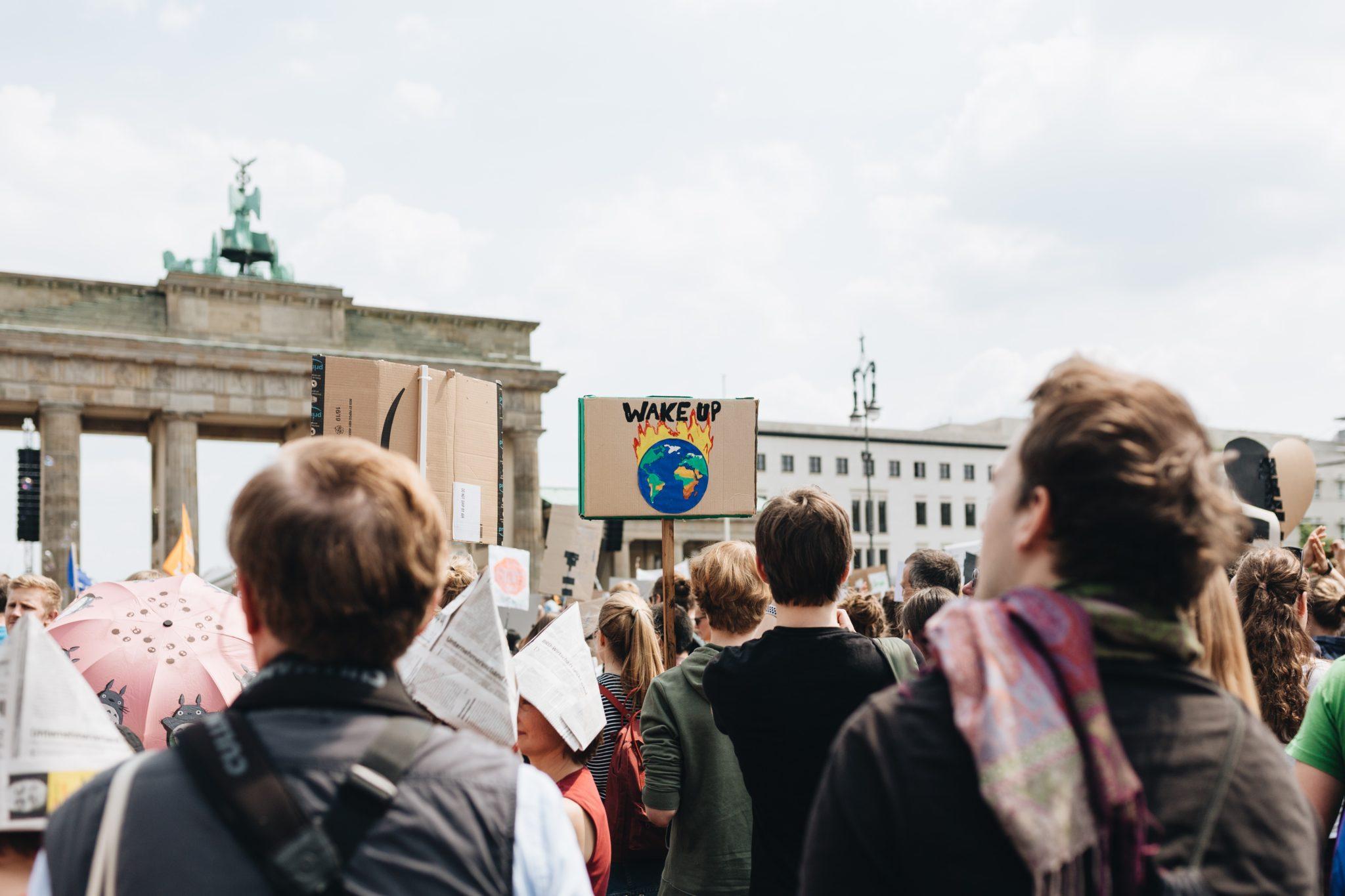 Schulstreikbewegung: eine Fridays for Future-Demonstration. Viele Menschen stehen vor dem Brandenburger Tor. Ein Demoschild mit einer brennenden Erde ragt aus der Menge heraus