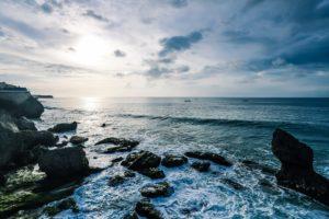 Küste mit Steinen im Wasser und leichten Wellen unter bedecktem Himmel
