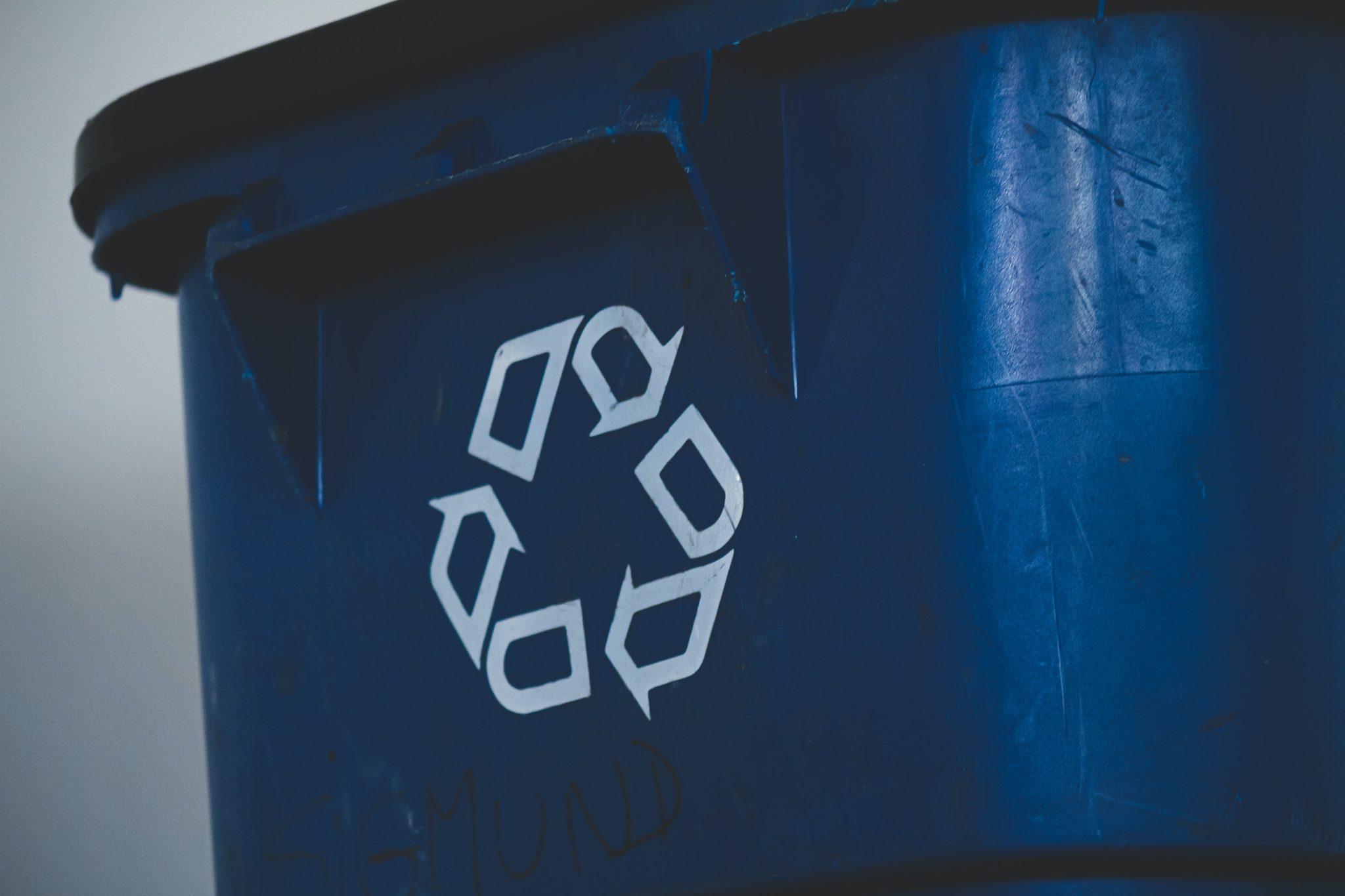 Eine schwarze Mülltonne mit einem weißen Recycling-Zeichen.