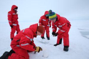 Vier Forscher:innen vom AWI in roten Anzügen knien im Eis und untersuchen es