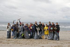 Gruppenfoto mit mehreren Menschen am Strand, die gefüllte Müllsäcke in der Hand halten