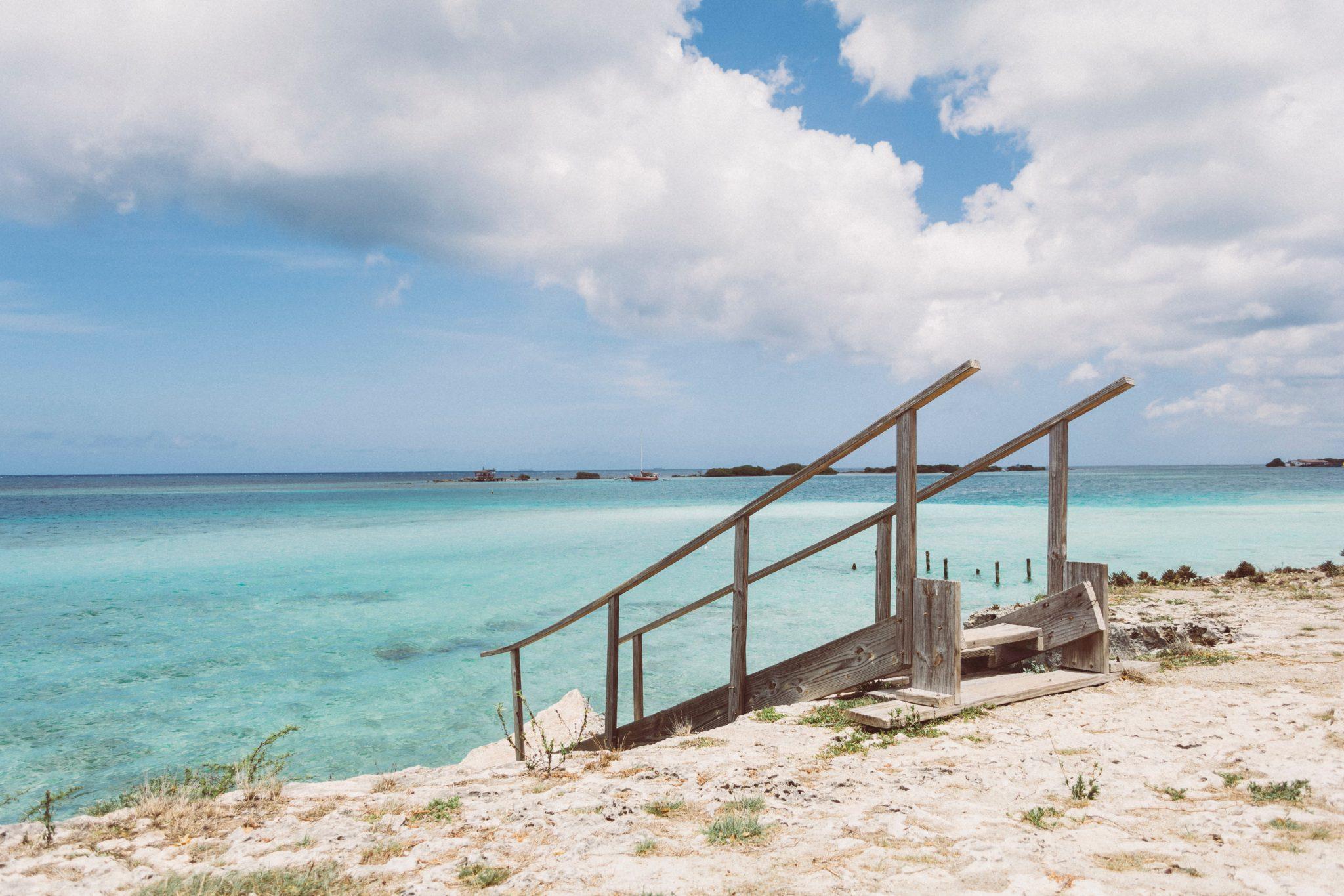 Eine Leiter führt vom Strand runter zum türkisenen Wasser in der Karibik