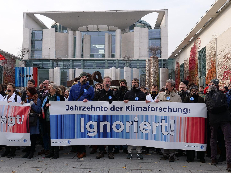 """Mehrere Menschen mit zugeklebten Mündern stehen vor dem Kanzleramt und halten ein Plakat von Scientists for Future hoch: """"Jahrzente der Klimaforschung ignoriert!"""""""