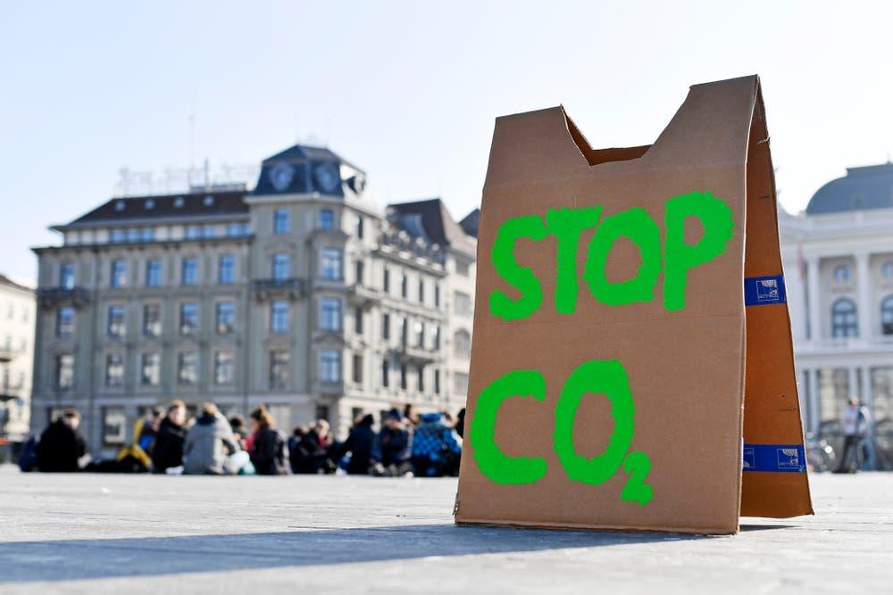 """Ein Schild mit """"Stop CO2"""" steht auf dem Boden auf einem öffentlichen Platz vor einer Gruppe sitzender Jugendlicher."""