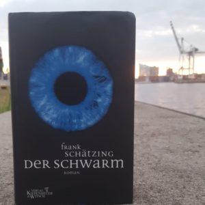 """Das Buch """"Der Schwarm"""" an einer Hafenkante mit Kran und Elbphilarmonie im Hintergrund"""
