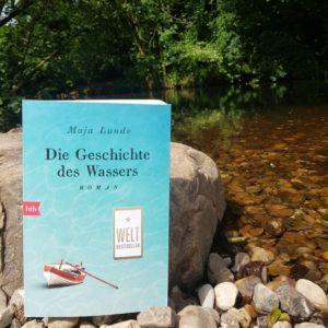 """Das Buch """"Die Geschichte des Wassers"""" an Ufer eines kleinen Flusses mitten in der Natur"""