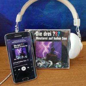 """Die CD zum Hörspiel """"Die drei Fragezeichen: Meuterei auf hoher See"""", ein Smartphone auf dem die Folge läuft und Kopfhörer"""