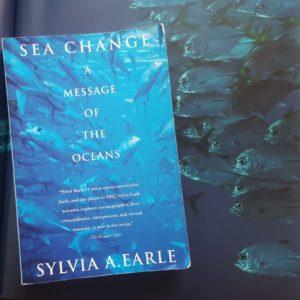 Das Buch Sea Change: A Message by the Oceans by Sylvia Earl mit einem Schwarm Fische im Hintergrund