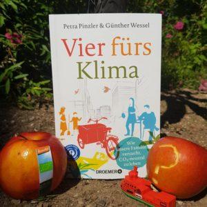 Das Buch Vier fürs Klima vor einem Fahrrad mit einem Bioapfel und einem konventionellen Apfel