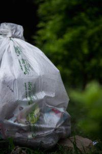 Eine abbaubare Plastiktüte steht auf dem Boden, gefüllt mit Müll.