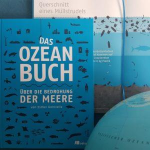 Das Ozeanbuch - Über die Bedrohung der Meere liiegt aufgesclagen, als auch mit dem Cover vor einem Globus