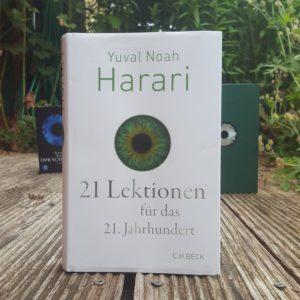 """Das Buch """"21 Lektionen für das 21. Jahrhundert"""" von Yuval Noah Harari ist zu sehen. Im Hintergrund sind weitere Bücher mit Augen auf dem Cover zu sehen."""
