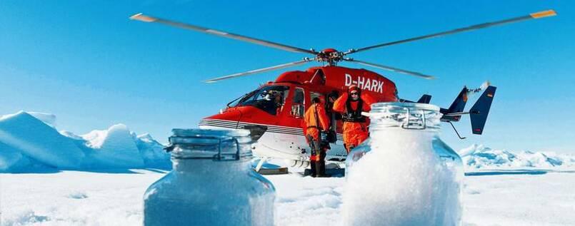 Ein roter Helikopter im arktischen Eis. Es ist strahlend blauer Himmel, im Hintergrund türmen sich Eisberge. Zwei Forscher mit dicken orangenen Überlebensanzügen stehen am Helikopter. Im Vordergrund sieht man zwei Weckgläser mit Schneeproben.