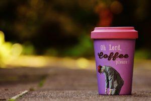 """Auf dem Boden steht ein pink-lilaner Coffee-to-go Bambusbecher mit der Aufschrift """"Oh Lord, Cofee please"""""""