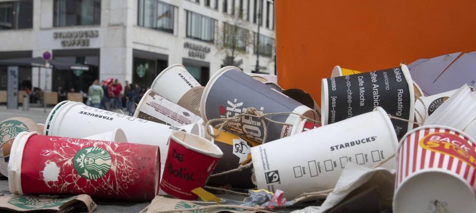 Viele leere Coffe-to-go Becher liegen an einer Straßenecke. Viele der Becher stammen von Starbucks. Im Hintergrund sieht man eine Starbucksfiliale