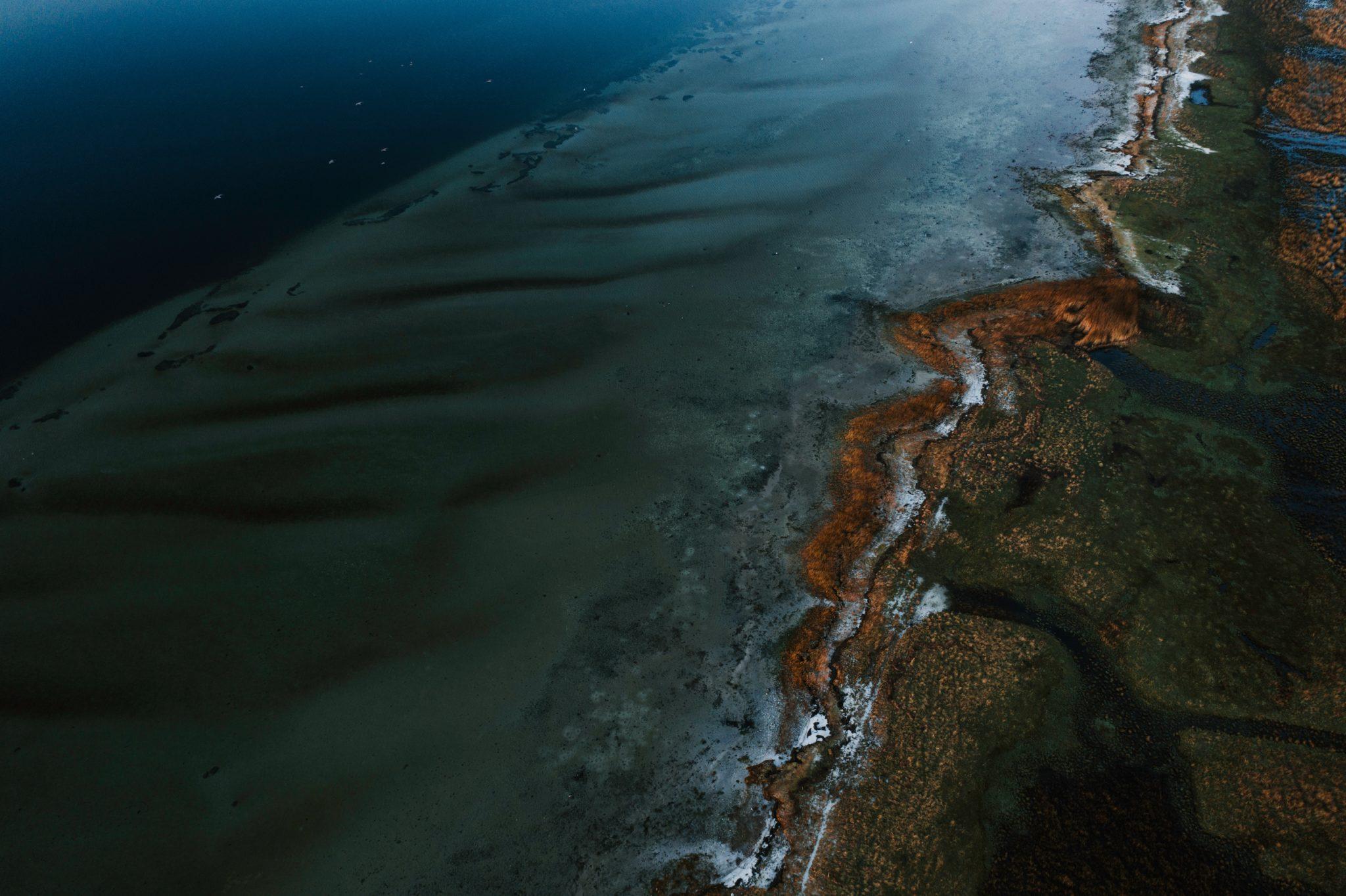 Eine Luftaufnahme von einer Küste, an der Öl ausgelaufen ist.