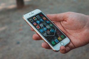 Eine Hand hält ein weißes Iphone, der Bildschirm zeigt viele verschiedene Apps