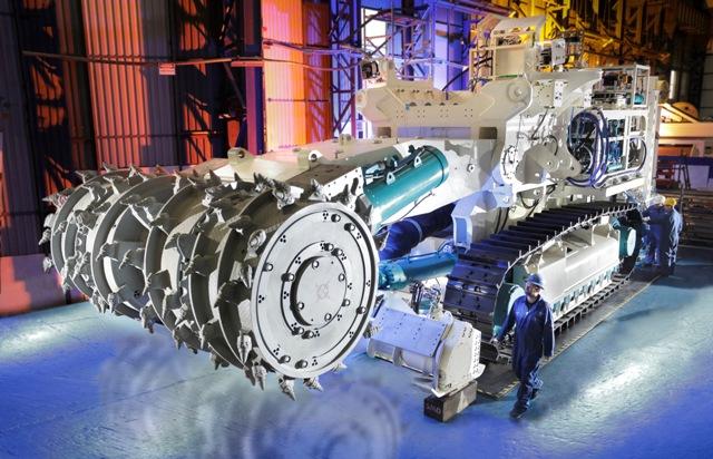 Eine riesengroße Maschine, die für den Tiefseebergbau eingesetzt werden soll, in einer Halle, mit einem Arbeiter, der winzig klein davor erscheint.