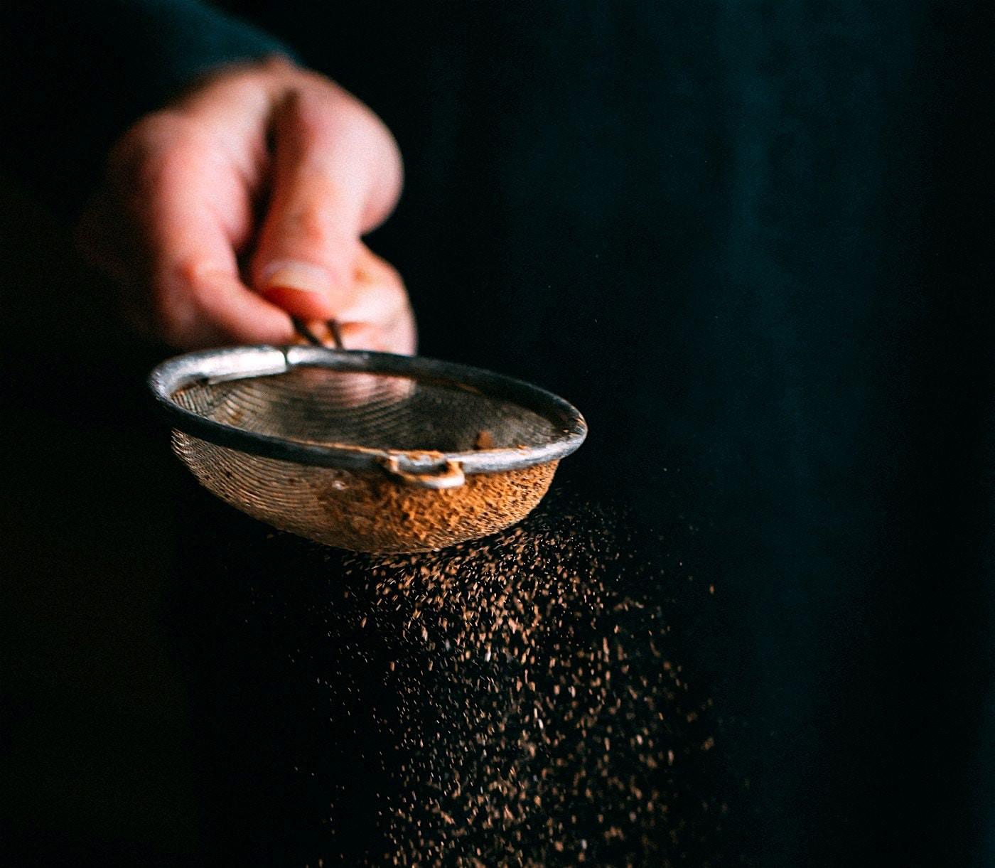 Eine Hand siebt Kakao aus einem kleinen Küchensieb