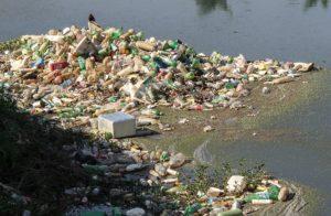 Ganz viel Plastikflaschen und anderer Müll liegt am Ufer. Das Wasser ist braun und wirkt schmutzig