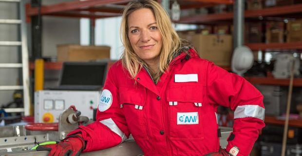 Das Bild zeigt eine blonde Frau in einer roten Jacke. Dabei handelt es sich um die Meeresbiologin Antje Boetius. Im Hintergrund sind verschiedene Messgeräte sowie ein aufgeklappter schwarzer Laptop zu erkennen.