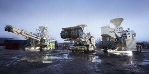 Es werden verschiedene Maschinen gezeigt, die im Meeresbodenbergbau eingestzt werden. Sie stehen auf schlammigem Untergrund, offenbar im Watt.