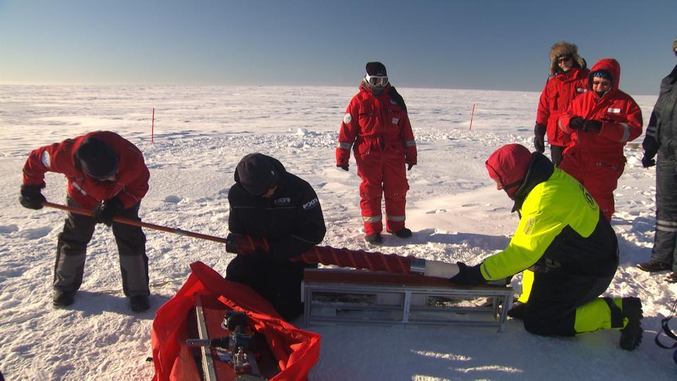 Das Bild zeigt sieben Wissenschaftler auf der zugefrorenen Ostsee. Alle tragen Schneeanzüge und entnehmen Eis aus dem Untergrund.