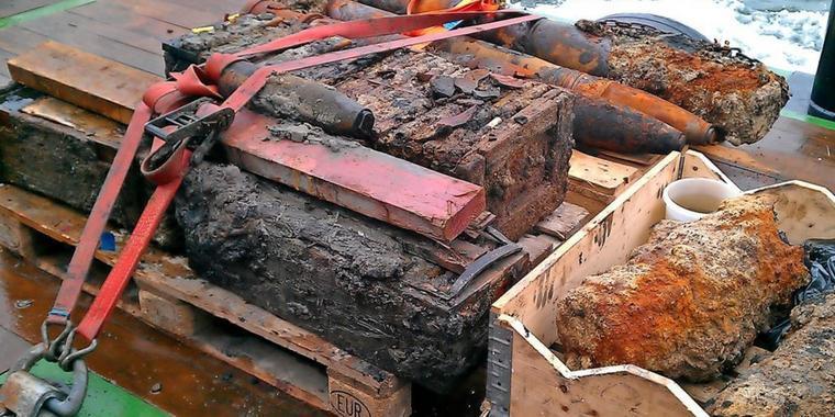 Viele alte Munitionslasten und Bomben wurden aus dem Meer geborgen. Sie liegen geordnet auf einem Stapel und sind mit einem Spanngurt befestigt. Sie sehen sehr alt aus und sind stark verrostet und verschmutzt