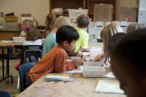 In einem Klassenzimmer beugen sich mehrere Kinder über einen Tisch, auf dem verschiedene Stifte und Papiere liegen.