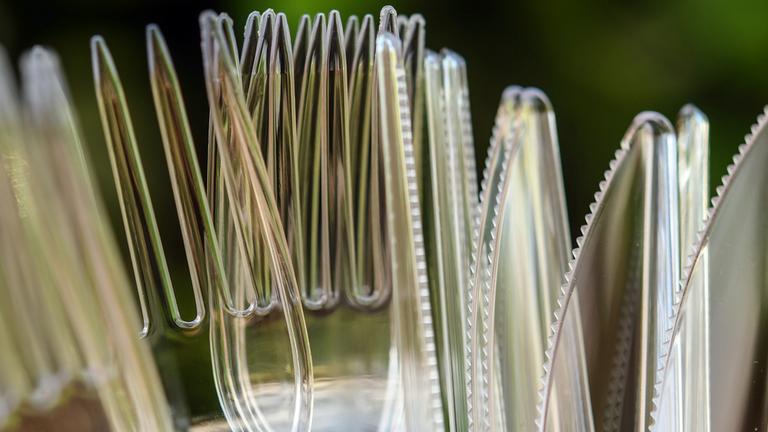 Die Spitzen von Plastikgabeln und -messern sind durcheinander zu sehen. Hinten ist ein grüner Hintergrund