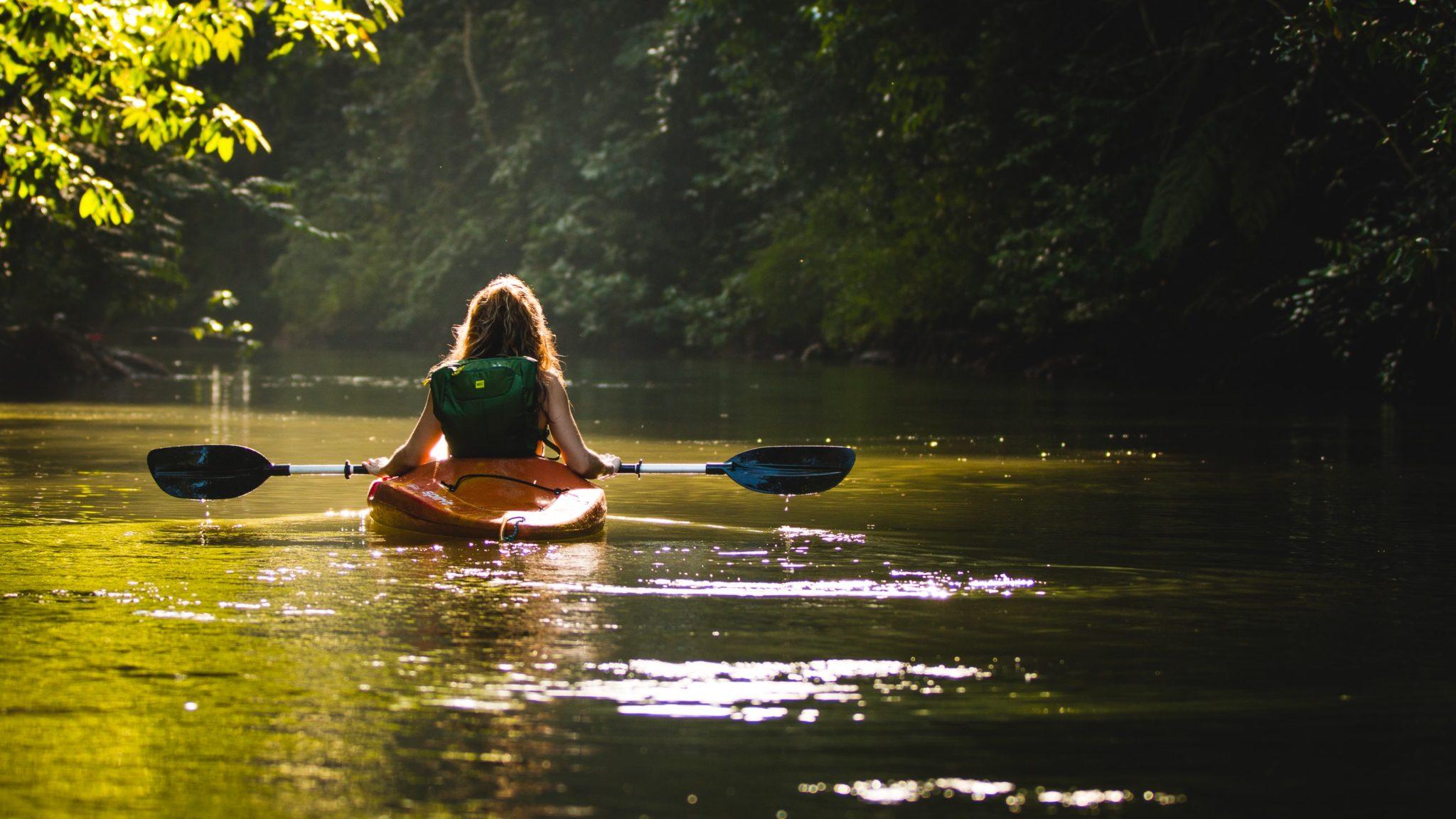 Eine Frau fährt mit auf einem Kajak über einen Fluss mit viel Bäumen an den Rändern