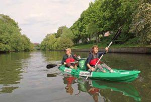 Zwei Personen auf einem grünen Kayak in Hamburg, ein Eimer für Müll steht zwischen ihnen