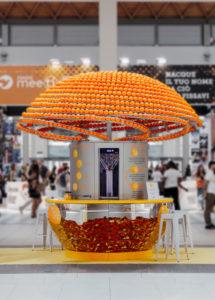 Eine riesige Orangensaftpresse. Im unteren Teil der Maschine liegen viele ausgepresste Schalen