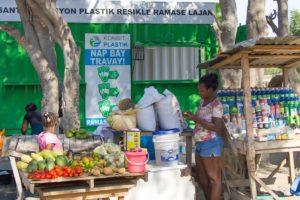zu sehen ist ein Marktstand in Haiti. Eine Frau hat mehrere Beutel Plastikmüll vor sich stehen. Links im Bild ist viel Obst auf einem Tisch aufbereitet. Rechts sind verschiedene Getränke und Kosmetikprodukte für den Alltag. Im Hintergund hängt ein großes Schild, welches zeigt, dass man Plastikflaschen gegen Geld oder verschiedene Gegenstäde eintauschen kann