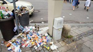An einer Straßenecke liegt unfassbar viel Müll auf dem Müllbehälter und daneben