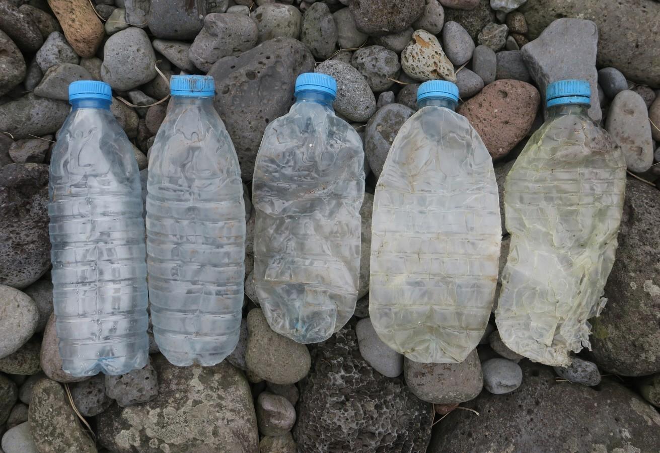 Fünf Einweg-Plastikflaschen liegen nebeneinander an einem Kiesstrand