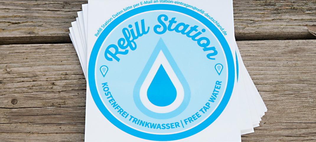 """Ein Stabel von """"Refill Sation"""" Aufkleber auf einem Holzhintergrund. In der Mitte des runden, blauen Aufklebers befindet sich ein großer Wassertropfen. Unter ihm befindet sich der Text: Kostenfrei Trinkwasser/Free Tap Water"""