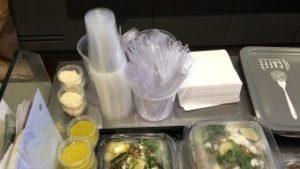 Plastikgeschirr (Becher, Besteck) liegen sauber geordnet auf einer Theke. Daneben stehen Servietten und Salatboxen, die in Plastik verpackt sind