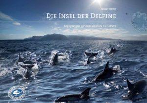 Das Cover des Buches. Eine Delfinschule schwimmt vor La Gomera und springt aus dem Wasser. Das Meer ist von knapp über der Wasseroberfläche fotografiert. Im Hintergrund sieht man die Berge der Insel. Titel: Die Insel der Delfine- Begegnungen auf dem Meer von La Gomera